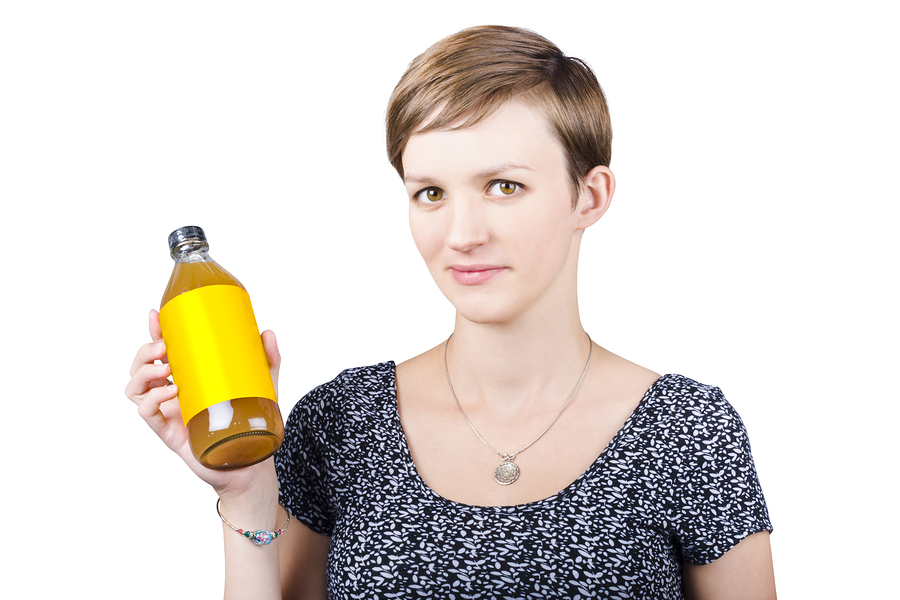 Woman Holding Glass Bottle Of Apple Cider Vinegar