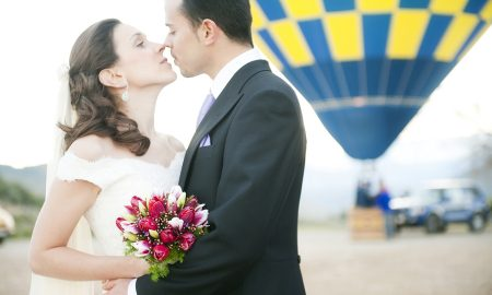 Young couple just married in a hot air balloon (focus on bouquet